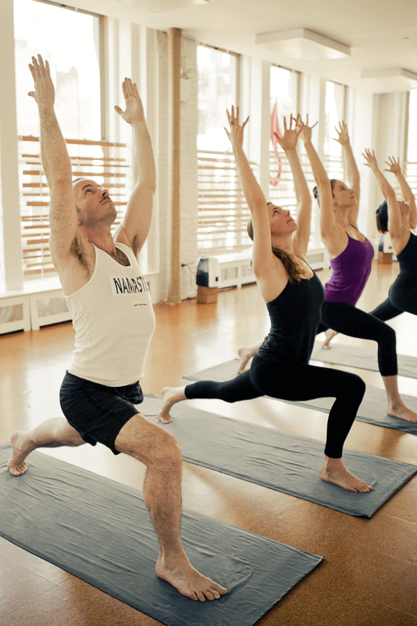 Yogis doing Warrior I in a Moksha yoga class