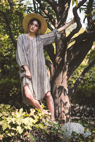 Loose fit dress with lantern sleeves, a shirt-tail hem, and a V-neck and coconut buttons | Love Faustine