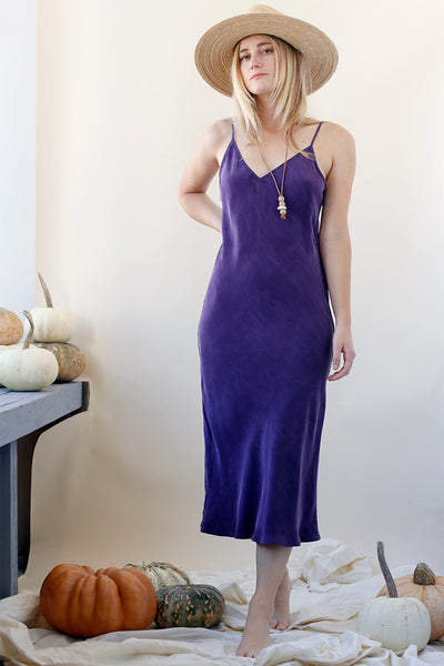 Girl in sustainable violet slip dress and wearing a hat for fall