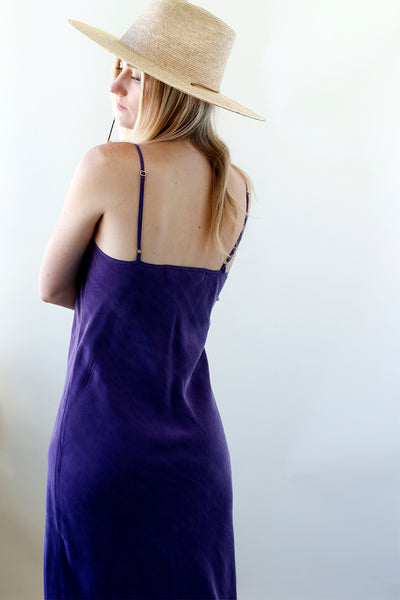 Girl show back of sustainable violet slip dress and wearing a hat for fall