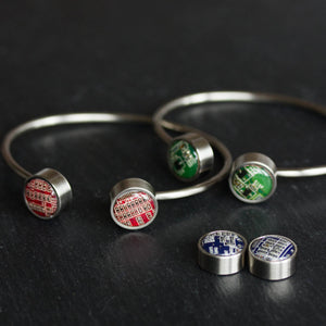 Bangle bracelet with interchangeable buttons