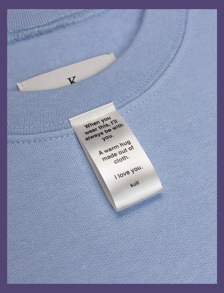 Close-up on the label of A WARM HUG Sweater in Light Blue by KULT Clothing | When you wear this, I'll always be with you. A warm hug made out of cloth. I love you. KULT