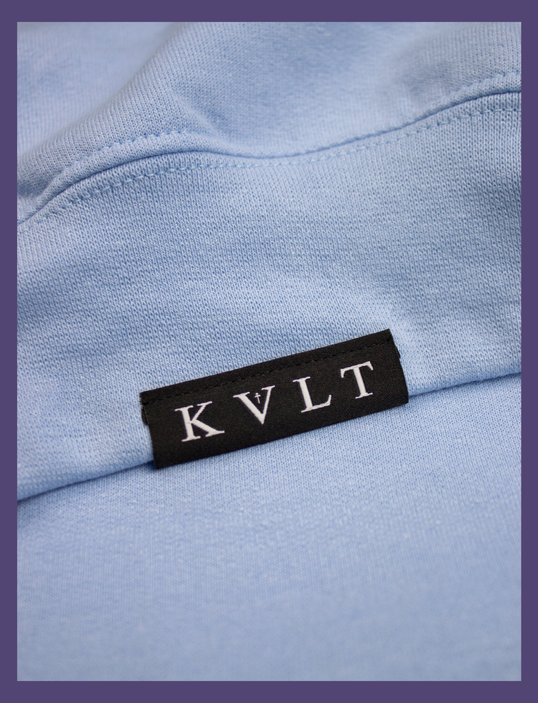 Close-up shot of the topside hem tag on the A WARM HUG Sweater in Light Blue by KULT Clothing | When you wear this, I'll always be with you. A warm hug made out of cloth. I love you. KULT | KVLT