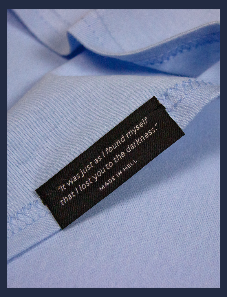 "Close-up on the underside of the bottom seam label of A WARM HUG Tee in Light Blue by KULT Clothing | ""It was just as I found myself that I lost you to the darkness."" Made in Hell."