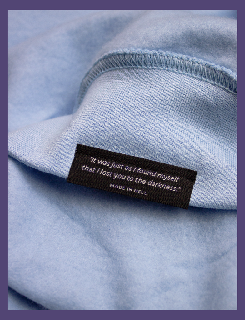"Close-up shot of the underside hem tag on the A WARM HUG Sweater in Light Blue by KULT Clothing | ""It was just as I found myself that I lost you to the darkness."" MADE IN HELL"