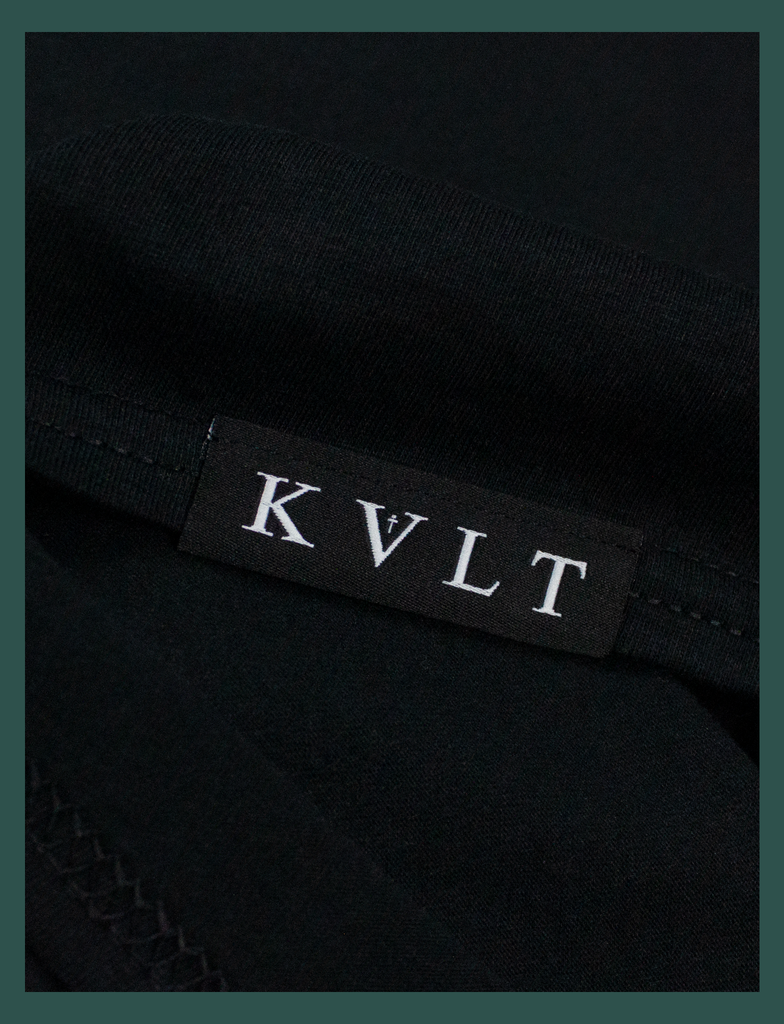 Close-up on the bottom seam label of A WARM HUG Tee in Black by KULT Clothing | When you wear this, I'll always be with you. A warm hug made out of cloth. I love you. KULT