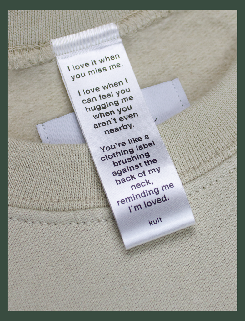 Close-up on the label of the DISTANT LOVE Sweater in Sandstone by KULT Clothing | I love it when you miss me.  I love when I can feel you hugging me when you aren't even nearby.  You're like a clothing label brushing against the back of my neck, reminding me I'm loved. KULT
