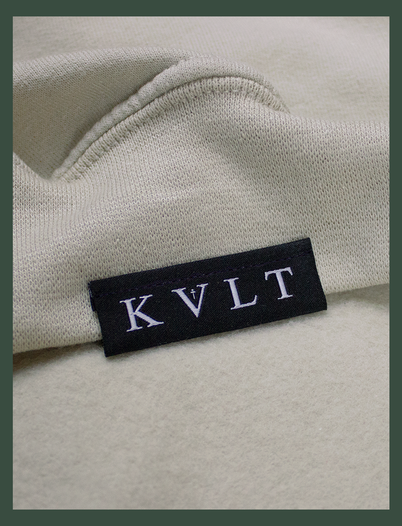 Close-up shot of the topside hem tag on the DISTANT LOVE Sweater in Sandstone by KULT Clothing | I love it when you miss me.  I love when I can feel you hugging me when you aren't even nearby.  You're like a clothing label brushing against the back of my neck, reminding me I'm loved. KULT | KVLT