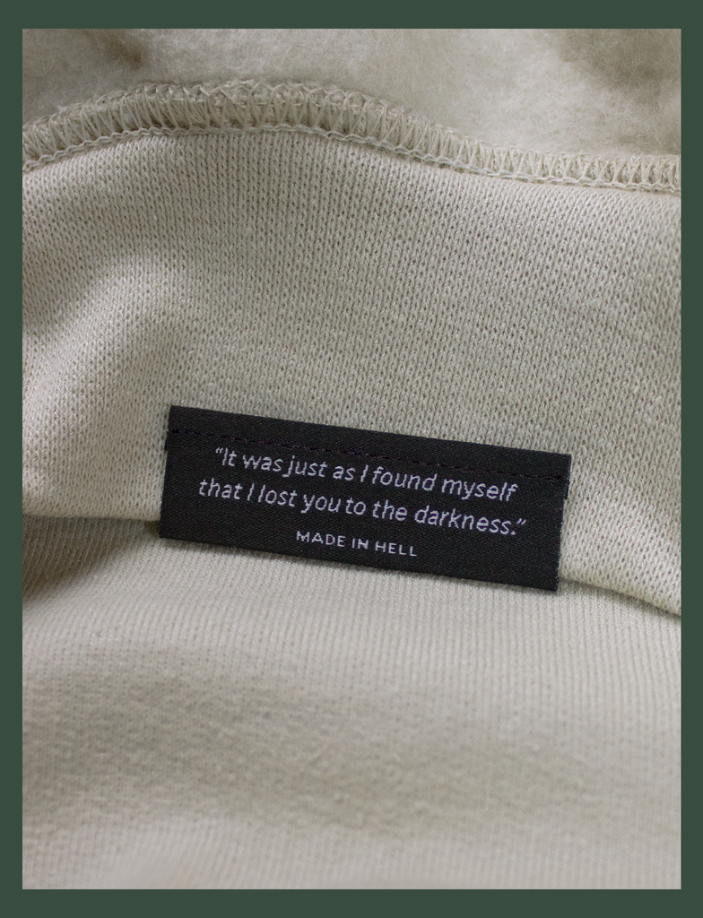 "Close-up shot of the underside hem tag on the DISTANT LOVE Sweater in Sandstone by KULT Clothing | ""It was just as I found myself that I lost you to the darkness."" MADE IN HELL 