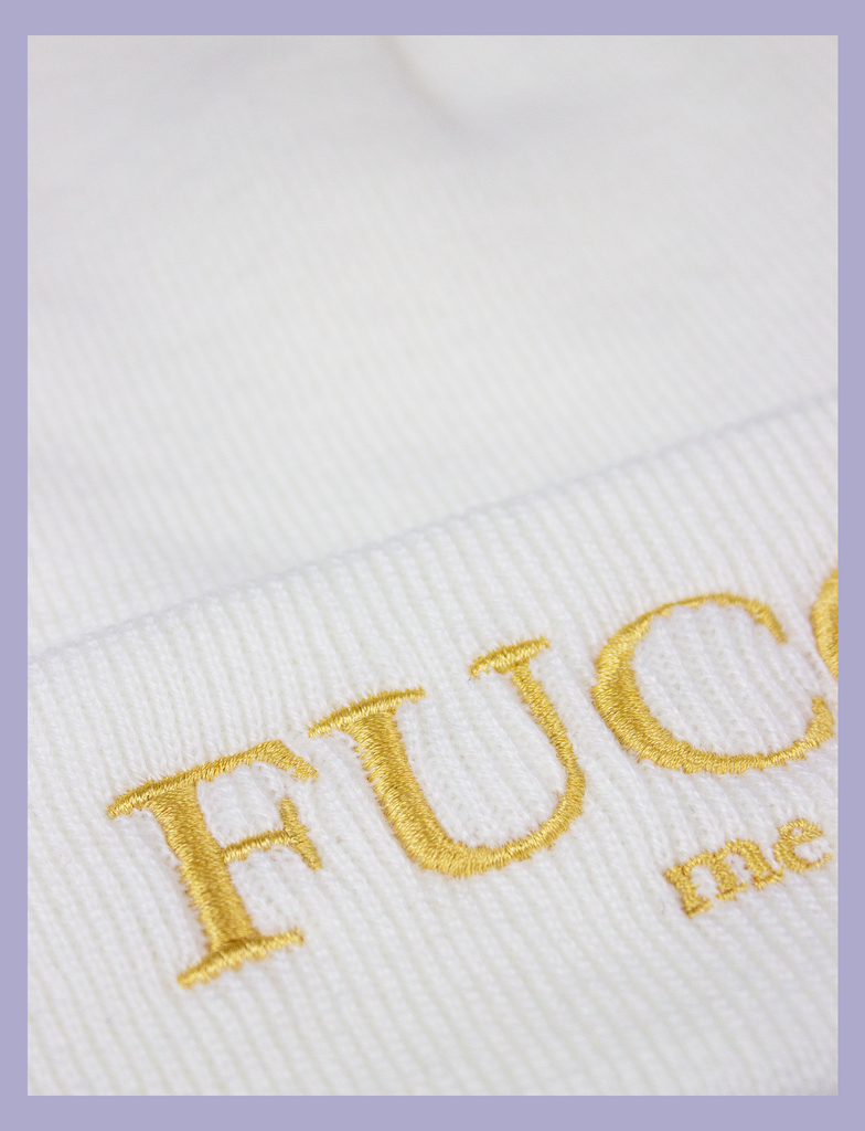 "Close-up of the design on the FUCCI ME Beanie by KULT Clothing | ""Fucci Me"" embroidered design in gold thread on a white acrylic beanie hat"