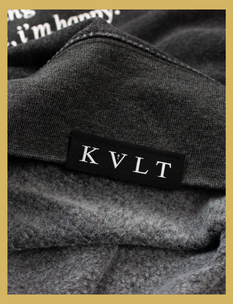 Close-up view of the topside hem label on the JOY Sweater by KULT Clothing | Aren't we all just doing stuff so we can get a hit of joy? What does it matter where you got that feeling, as long as it isn't hurting anyone else? Leave me be, I'm happy.