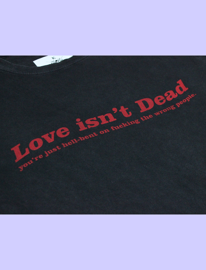 Close-up of the LOVE ISN'T DEAD Tee in Sun-Bleached Black by KULT Clothing | eco-friendly, climate neutral t-shirt | Love isn't Dead you're just hell-bent on fucking the wrong people.