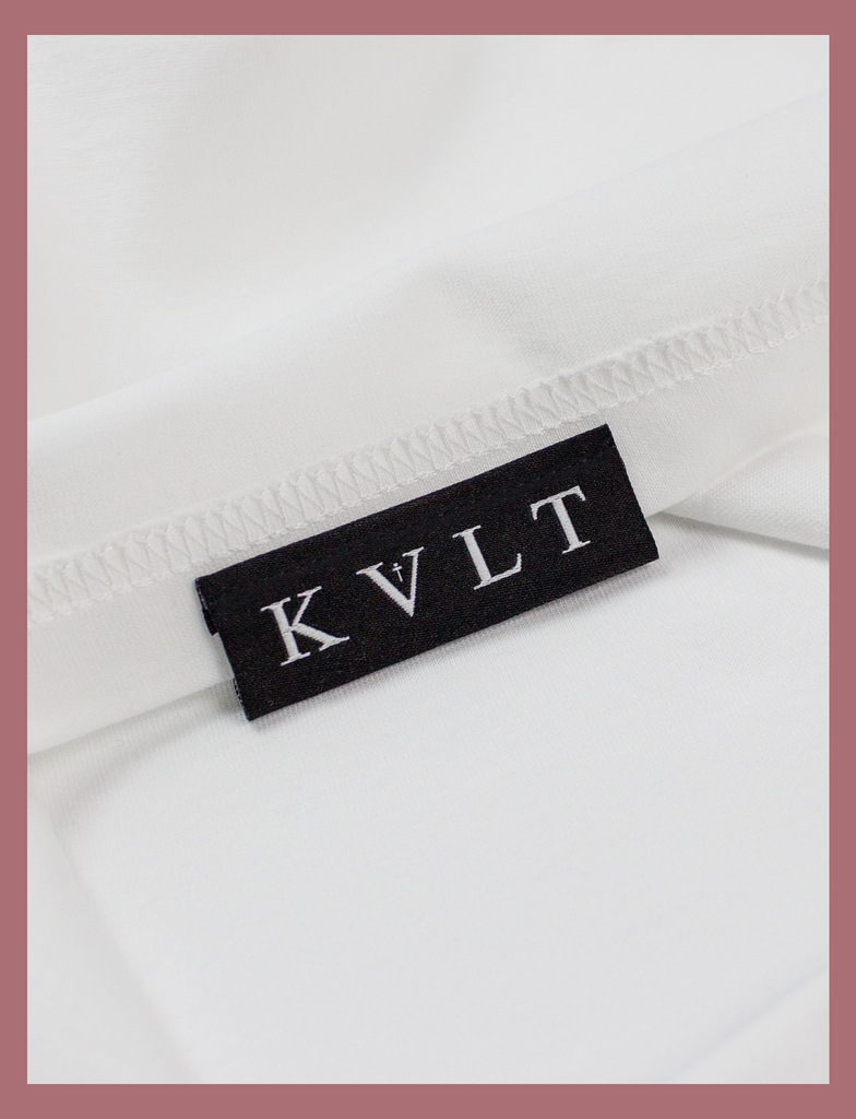 Close-up view of the topside hem label on the SUNSHINE Tee by KULT Clothing | Sunshine on my skin, I feel me again.