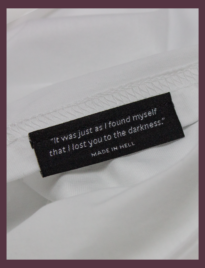 Close-up of the underside hem label on the SUNSHINE Tee by KULT Clothing | You Should Take A Moment To Stop And Look Around Every Once In A While. There's Some Awful Shit Going On. KULT