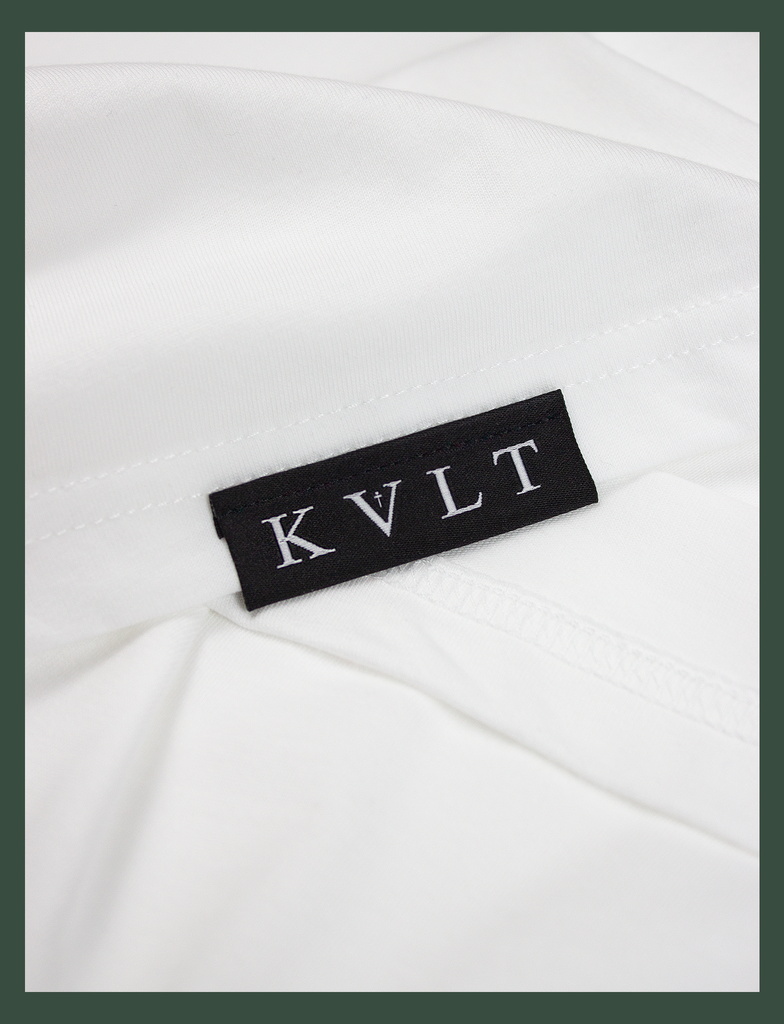 Close-up shot of the topside hem tag on the TIL DEATH Tee in White by KULT Clothing | eco-friendly, climate neutral t-shirt | 'til death, we do art. | till death we do art