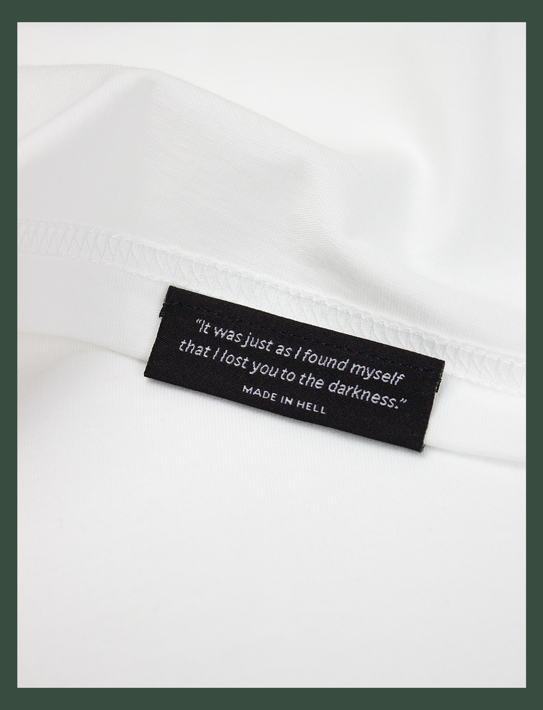"Close-up shot of the underside hem tag on the TIL DEATH Tee in White by KULT Clothing | eco-friendly, climate neutral t-shirt | ""It was just as I found myself that I lost you to the darkness."" MADE IN HELL"
