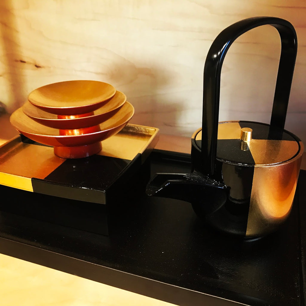 A photo of a black and gold lacquered Japanese sake set which consists of a serving pot, two dish-like cups, and a tray