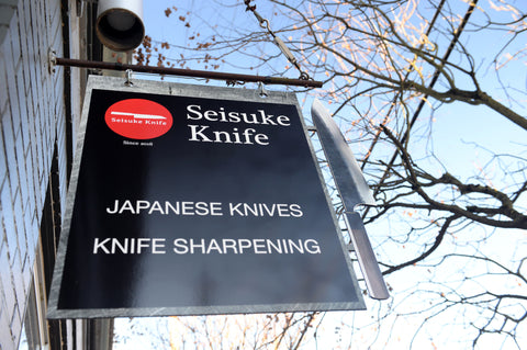 A photo of the store's sign that reads: Seisuke Knife Japanese Knives, Knife Sharpening