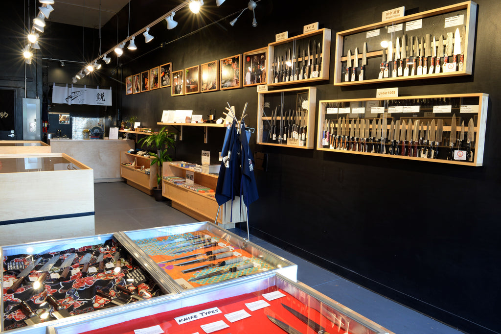 A photo of the Seisuke Knife Portland shop interior showing display cases on the walls and tables containing a large selection of knives