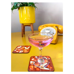 Customer photo - Atomic Boomerang Coasters on yellow table with Babycham cocktail, vintage telephone and retro planter | The Inkabilly Emporium