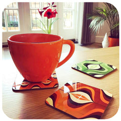 &0s Op Art Coasters in Orange and Green on table with tea cup