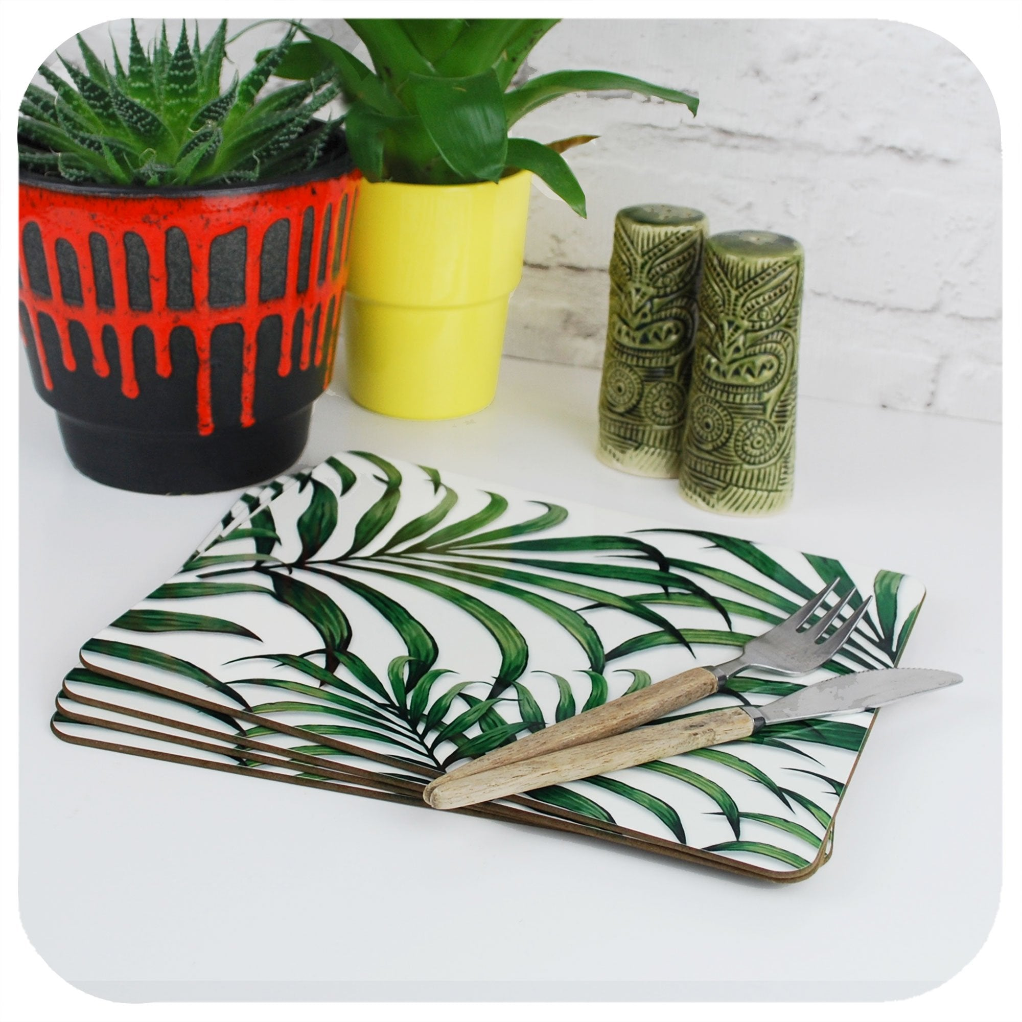 Palm Leaf Print Placemats, set of 4 on a table with tropical plants and Tiki cruet set | The Inkabilly Emporium