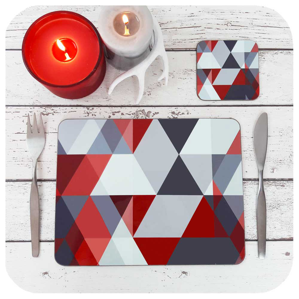 Scandi Geometric placemat and matching coaster, in red & grey. Set on a table with festive candles and christmas table decor | The Inkabilly Emporium
