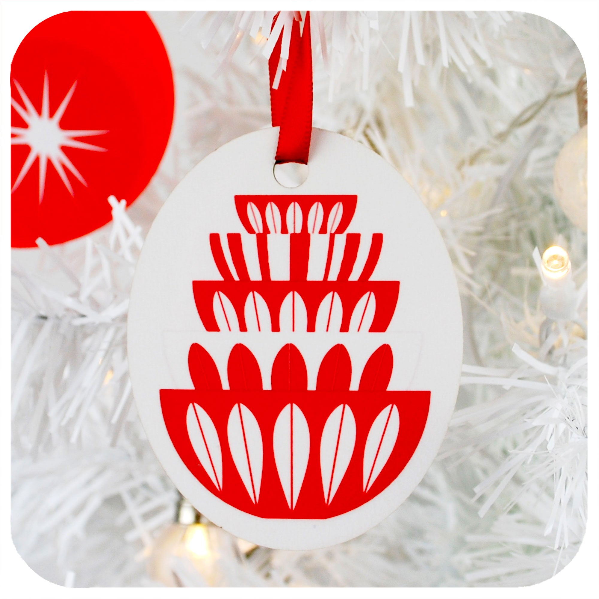 Christmas Tree Decoration featuring graphic of Catherineholm Bowl Stack in white & red, hanging by red ribbon on a white Christmas tree | The Inkabilly Emporium