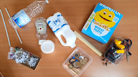 Image of a cereal box, water and milk bottles and some sticks on a wooden table.
