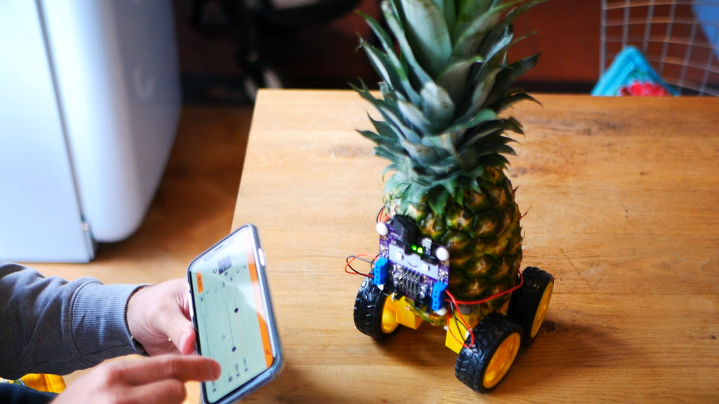 Completed pineapple robot with smartphone in foreground showing Smartibot app control pad mapping editor