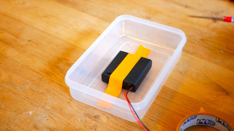 Image of a black battery box taped down inside a Tupperware container with orange tape