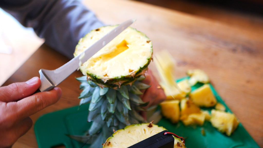 Chunks of pineapple are removed from a rectangular hole in the underside of the top section of the fruit