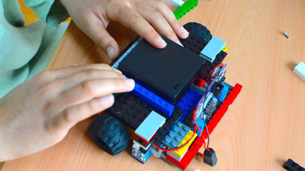 A picture of a two hands assembling a structure around a battery pack with LEGO