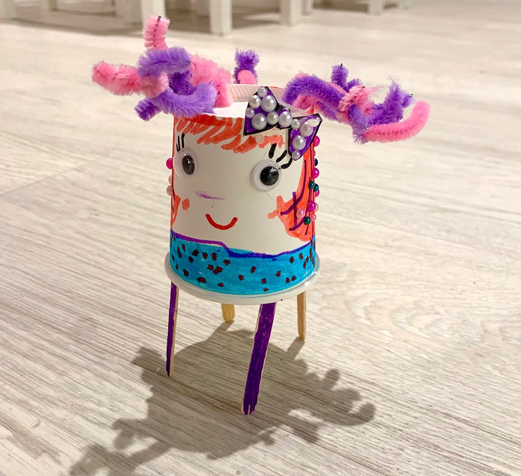 Paper cup based robot with face with two goggly eyes, drawn on eyelashes and pink hair, a light blue body with black spots, plus pink purple pipe cleaner hair and four purple coffee stirrer legs