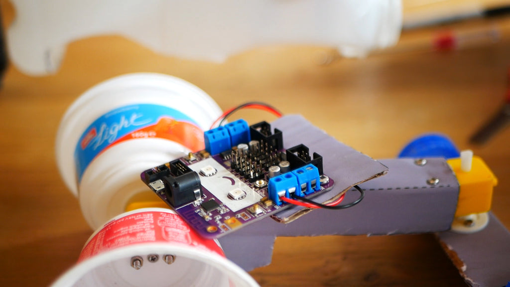 Image of a purple circuit board with a smiley face connected to black and red wires, laying on a cardboard structure.
