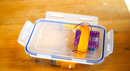 Image of a purple circuit board taped on a Tupperware container lid with orange tape