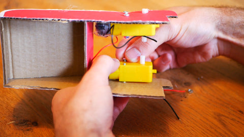 Image of a yellow motor being screwed on to a red cardboard structure.