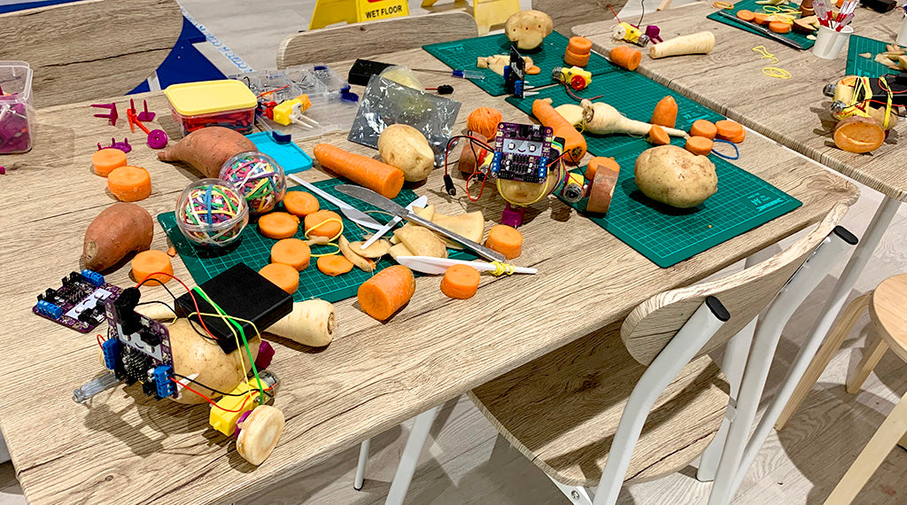 Photo of a messy table covered with potato, carrots and parsnips, electronics and tools, plus three potato robots.