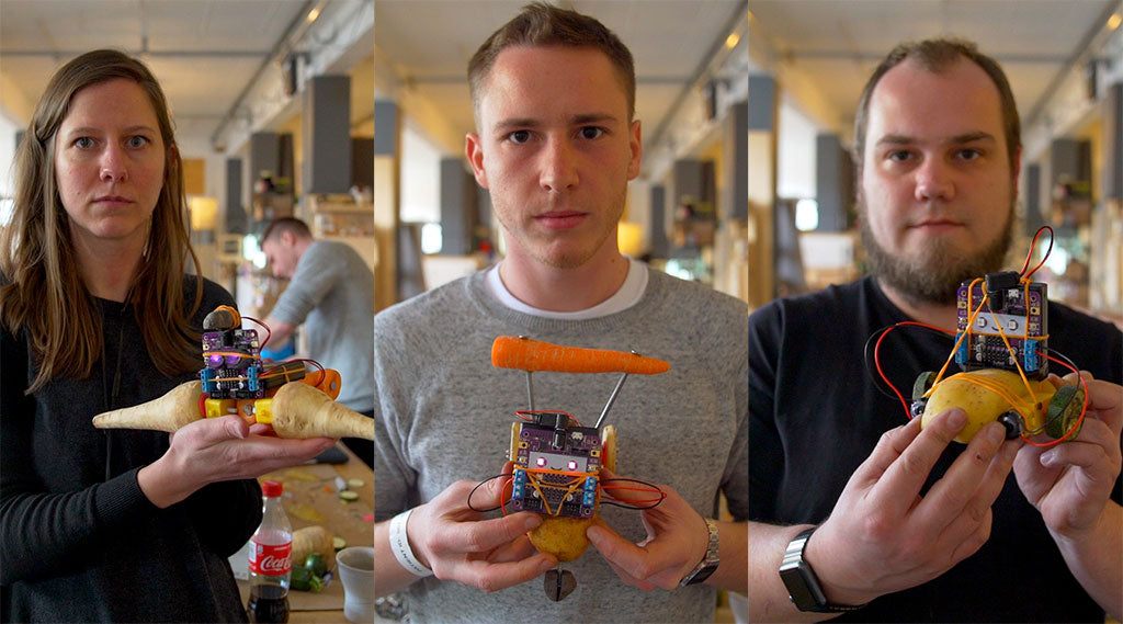 Three young adults holding robots made from vegetables and staring intently into the camera