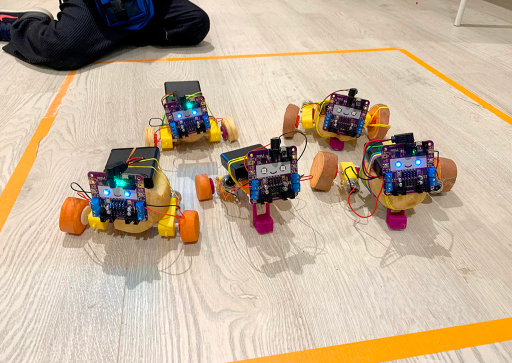 Five robots made from potatoes and vegetables on the floor inside a square made from orange tape