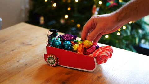 An image of a chocolate filled Christmas sleigh, as someone is picking up one chocolate.