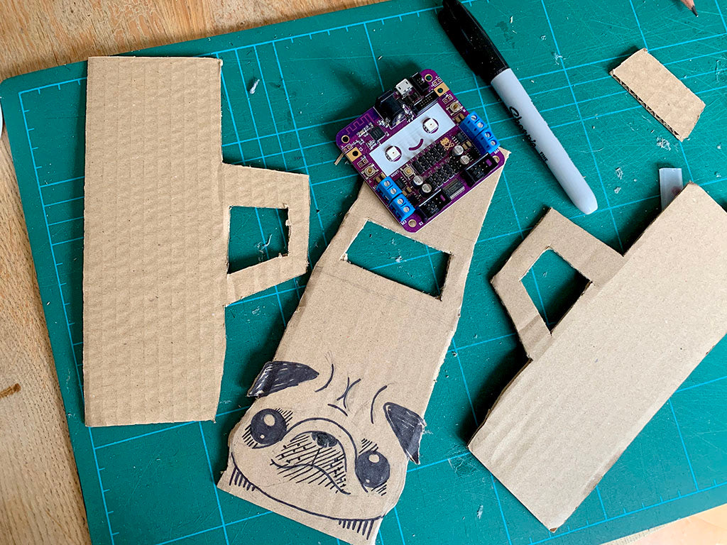 Photo of some cardboard monster truck parts, a purple smiling circuit bard and a black marker pen on a cutting mat