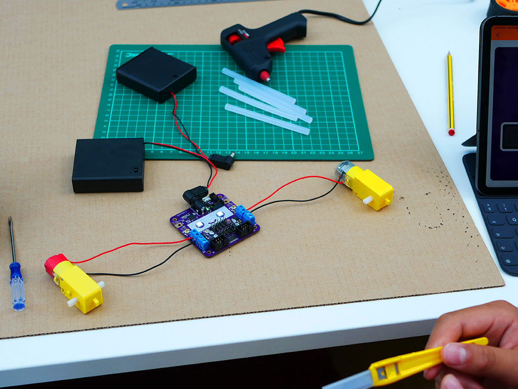 Photo of a Smartibot circuit board connected to two motors and a battery box, lying on a large sheet of cardboard. In the background a cutting mat, glue gun and hot melt glue sticks
