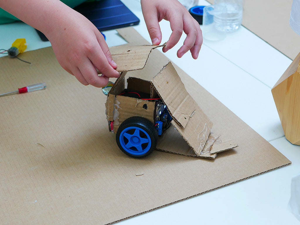 Photo of a cardboard robot chassis like in the example to which a young person is adding extra cardboard parts to form a narrow wedge.