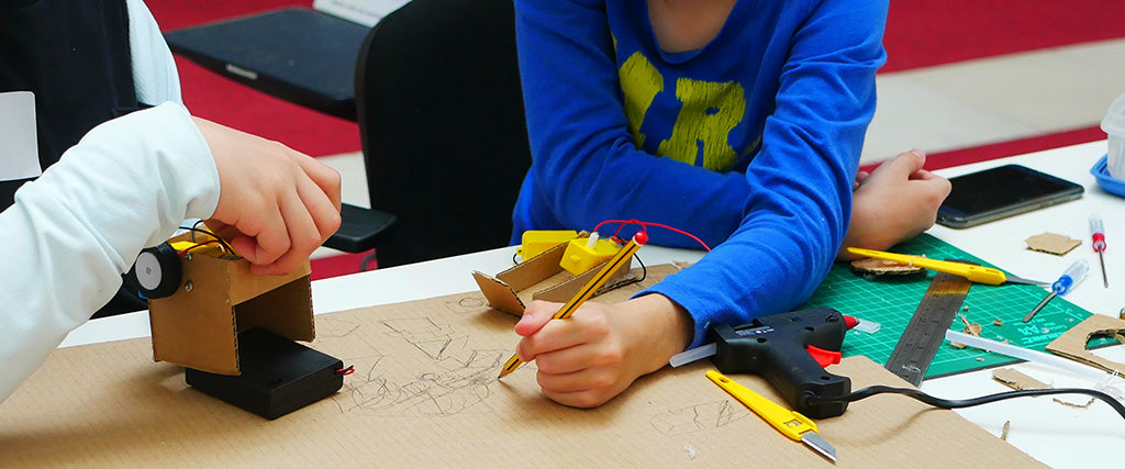Photo of two young people collaborating to build a cardboard robot. One sketches in pencil on a piece of cardboard whilst another holds a partially completed robot.