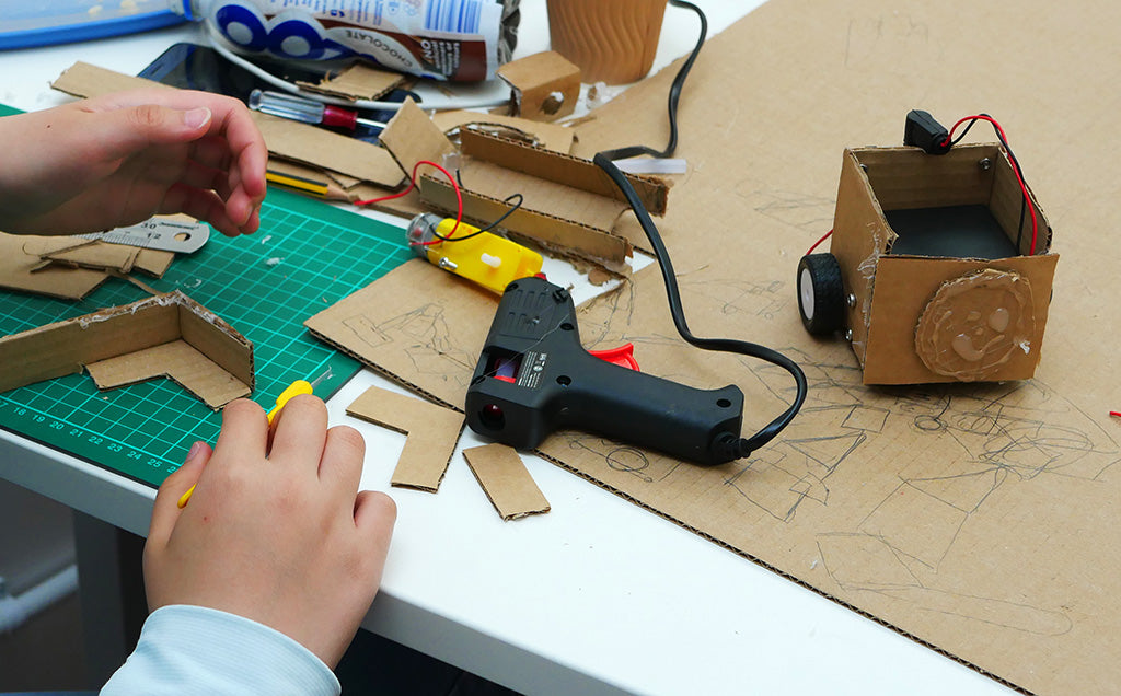 Photo of a partially completed cardboard robot with some intricate cardboard pieces being assembled with a hot glue gun in the foreground. A motor and some tools lie in the background.