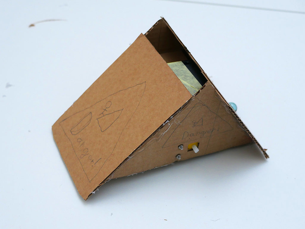 Cardboard robot in the form of a wedge, decorated on the front and side with pencil drawings of a stick man being attacked by a triangle and the word 'Danger!' inside a triangle.