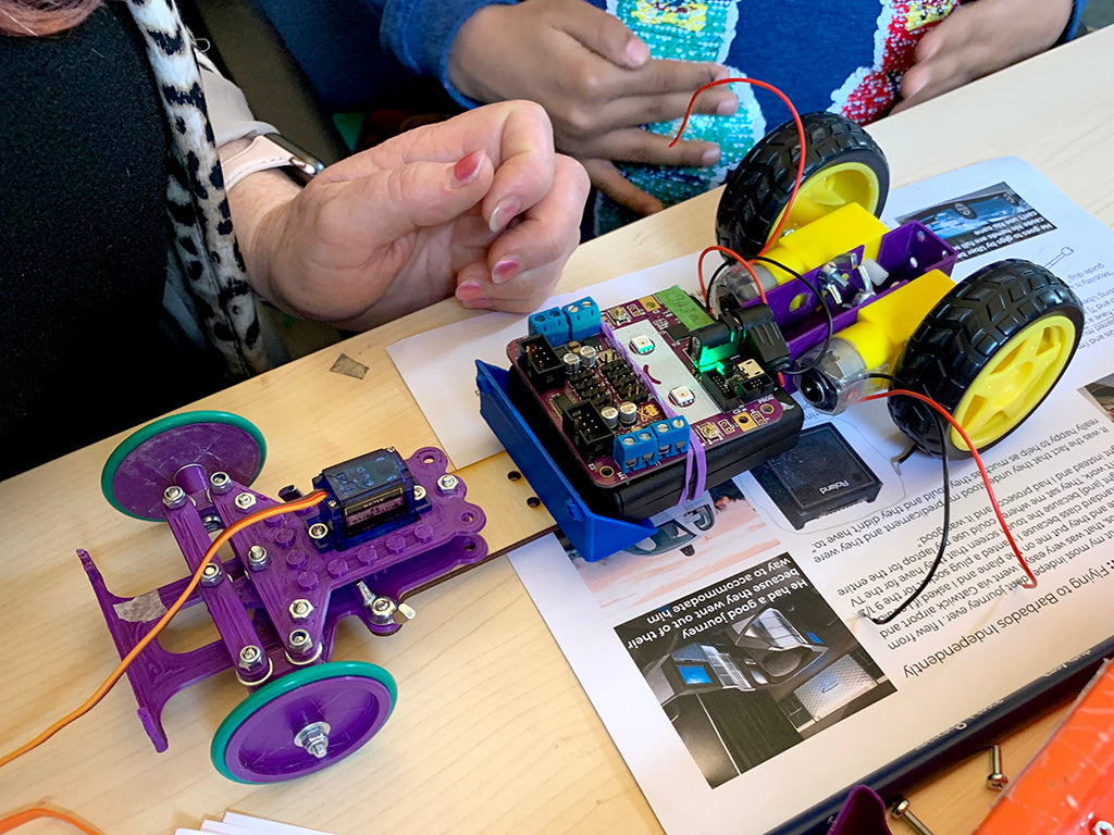 Photo of a small car chassis with a purple plastic steering mechanism and wheels at the front, two yellow plastic motors and wheels at the back and a smiling purple circuit board in the centre