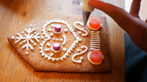 Image of a gingerbread house wall being decorated with white icing and red gumdrops.
