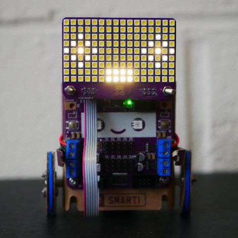 Smartibot with an LED matrix attached to the top displaying a face with dull eye outlines, bright pupils and a bright, rectangular mouth